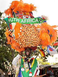 A man in costume wears a large decorated hat in Cape Town during the 2010 World Cup, South Africa