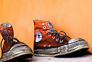 Old used and soiled orange Converse All Star shoes on an orange background