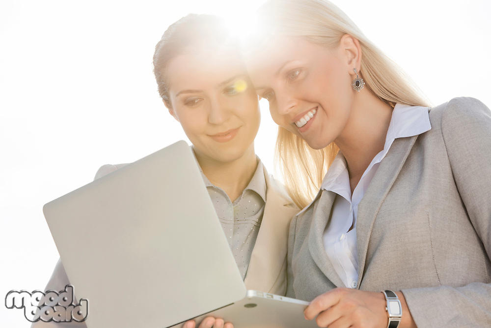 Happy young businesswomen using laptop against sky