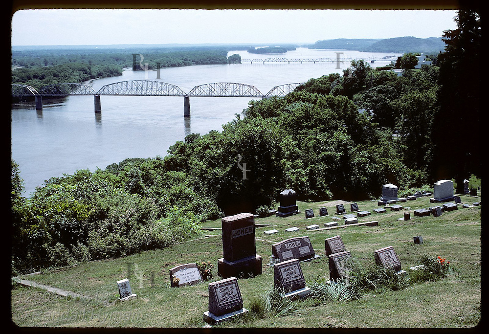 Like sentinels on a bluff, gravestones stand watch as Mississippi River passes; June, Louisiana. Missouri