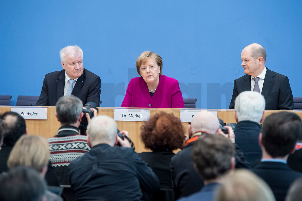 12 MAR 2018, BERLIN/GERMANY:<br /> Horst Seehofer (L), CSU, desig. Bundesinnenminister, Angela Merkel (M), CDU, Bundeskanzlerin, und Olaf Scholz (R), SPD, desig. Bundesfinanzminister, waehrend einer Pressekonferenz zum Koalitionsvertrag der CDU/CSU und SPD, Bundespressekonferenz<br /> IMAGE: 20180312-01-020
