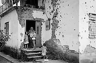 A family consisting of only women in an house that shows evident scars of the war.