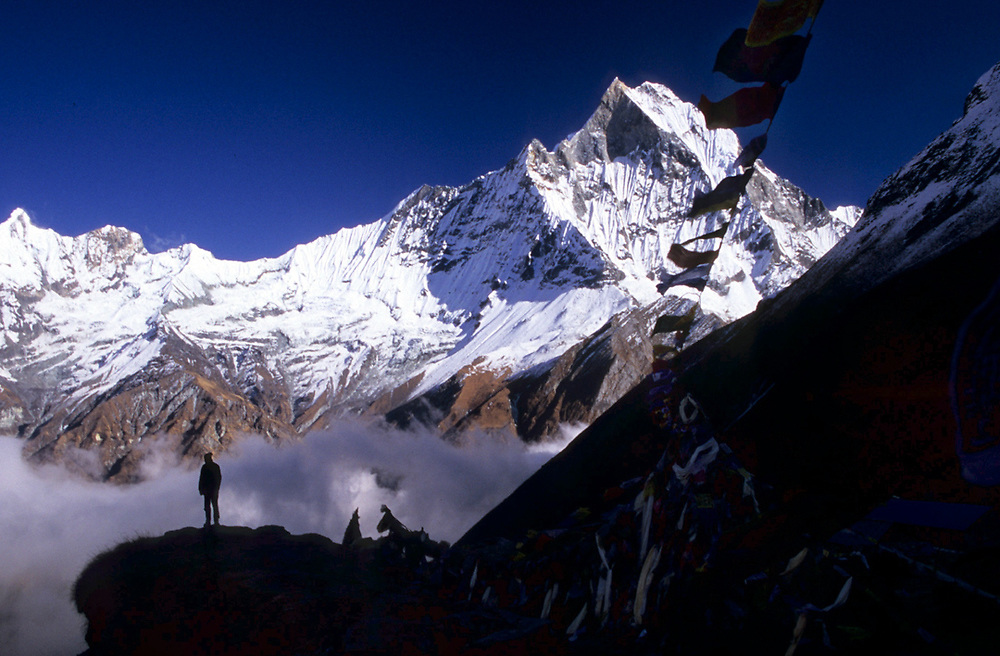 A man in the distance is watching the panorama from the Annapurna base camp at  4,130mt, in the north central Himalayas of Nepal. Furthest in the background and marked with snow is the Machapuchare mountain, sacred to the God Shiva and therefore off limits to climbing. <br />