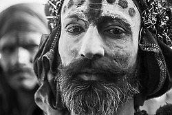Close up black and white portrait of a man staring into the camera with a decorated face painted for the camel fair,,Pushkar camel fair, Rajasthan, India