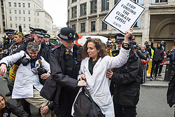 London, UK. 14 October, 2019. Police officers hold Dr Emily Grossman of Scientists for Extinction Rebellion who had blocked the busy junction at King William Street in front of London Bridge on the eighth day of International Rebellion protests across London. Today's activities were concentrated around the  City of London's finance district.