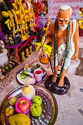 "03 MARCH 2013 - BANGKOK, THAILAND:   A plate of fruit left as an offering at the Chuchok Shrine. The Chuchok Shrine is in suburban Bangkok. More than 100 people a week come to the shrine to pray for good fortune or good health. People whose prayers are answered return to the shrine with ""coyote dancers"" to make merit and thank Chuchok. Coyote dancing is a Thai phenomenon created after the US movie ""Coyote Ugly"" where attractive young women dance in a sexually suggestive way, usually for pay. They're common at bars and festivals. Coyote dancers are typically better paid than other Thai women in the hospitality industry and usually are not allowed to date or see customers are off the dance floor. Coyote dancers perform at the Chuchok shrine because according to Buddhist literature Chuchok was a relatively repulsive old hermit and Brahmin priest who was cared for by a young woman after he made her family's wishes come true. PHOTO BY JACK KURTZ"
