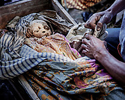 A family member opens the coffin of a dead relative for cleaning and grooming.<br /> <br /> Ma'nene is a tradition that takes place in August after harvest where the bodies of the dead loved ones are exhumed to be cleaned, groomed and dressed. For most, it's a bittersweet moment, a chance to reunite and physically see and touch and reconnect with loved ones who had passed on.