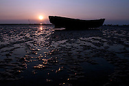 The sun sets behind a silhouette of a fishing boat in Chittagong, Bangladesh.