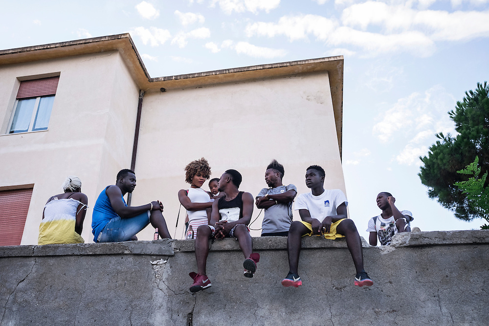 A group of western african (Nigeria, Gambia, Sierra Leone) refugees and asylum seekers talking while watching a football match in Riace. RIACE 01/08/2016
