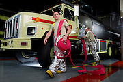 A U.S. Air Force firemen attach a hose to the fire engine...Firemen in the Air Force must extinguish aircraft building and brush fires. They must be prepared at all times for aircraft emergencies..