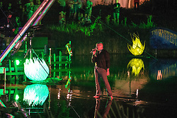 Image ©Licensed to i-Images Picture Agency . 17/07/2014 . Henham Park , Suffolk , United Kingdom . Jamie Irrepressible of the Irrepressible's performs from a floating platform in Henham Lake , next to an illuminated lily pad . The Latitude Festival of music and arts . Picture by Joel Goodman/i-Images
