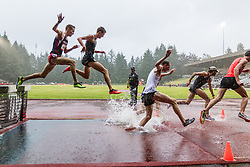 mens 3000 meter steeplechase splashes through rain and water on a night when runners hoped to reach the Olympic Trials qualifying time