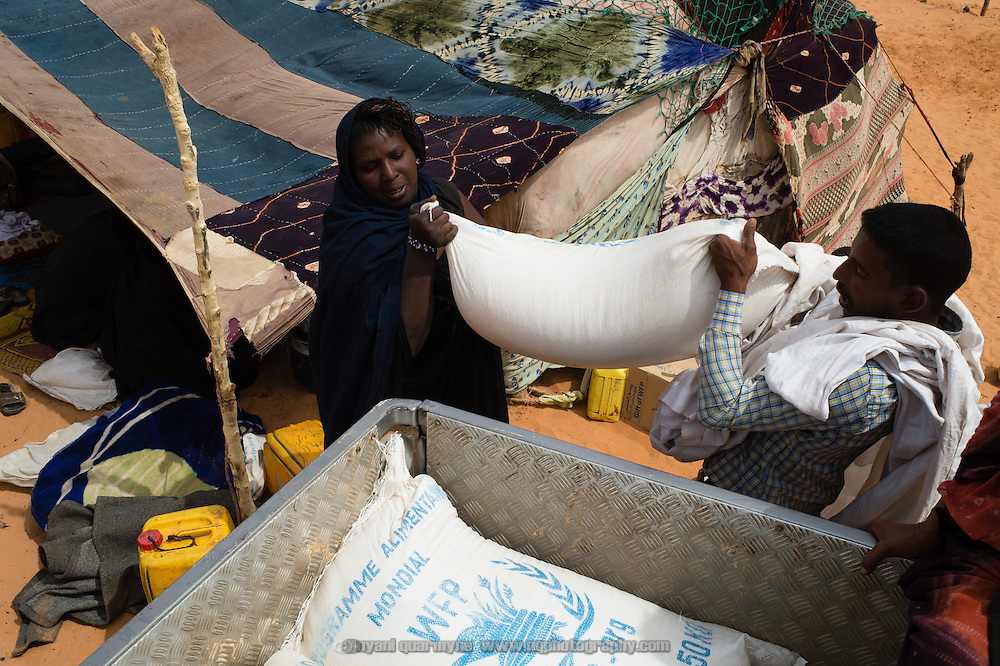 A recently arrived refugee from Mali (left) is helped to load her rations of rice, oil and sugar onto a pick-up at the Mbera refugee camp for Malian refugees in southeastern Mauritania on 2 March 2013. The majority of the camp's residents are accustomed to a staple diet of goat, camel or cow's milk and meat, but the UNHCR-provided rations do not include these - malnutrition is a growing concern, particularly amongst under fives.