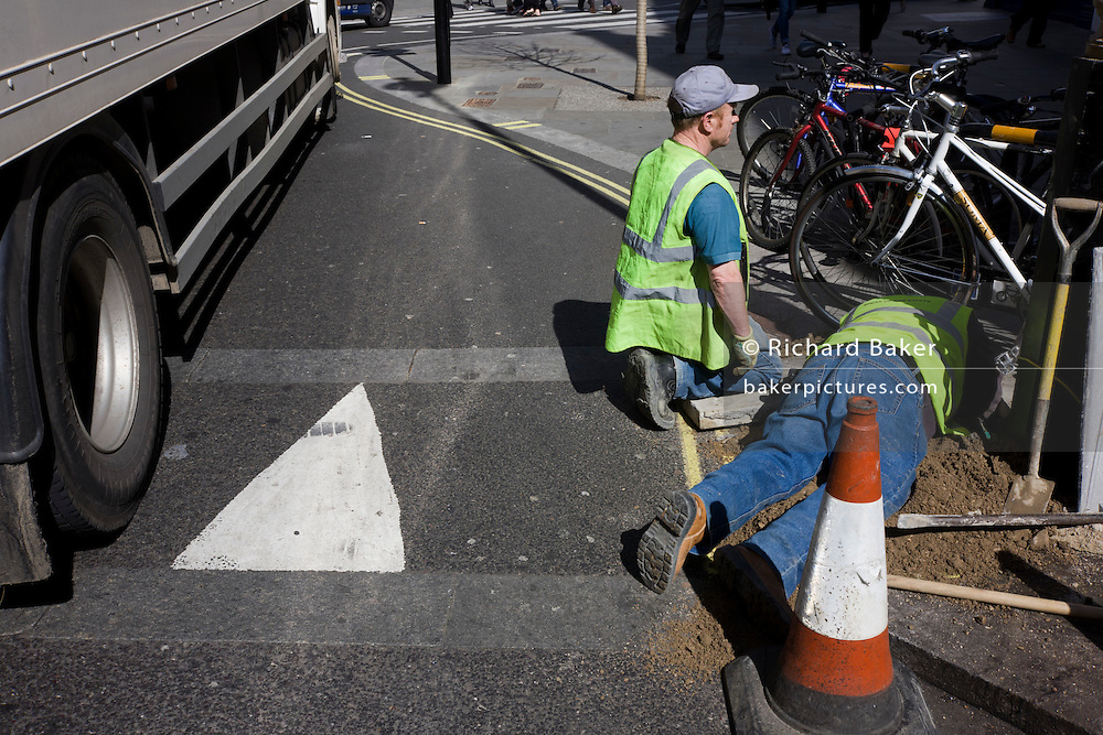 Contractors on roadworks in the road near passing HGV lorry (truck) in central London..