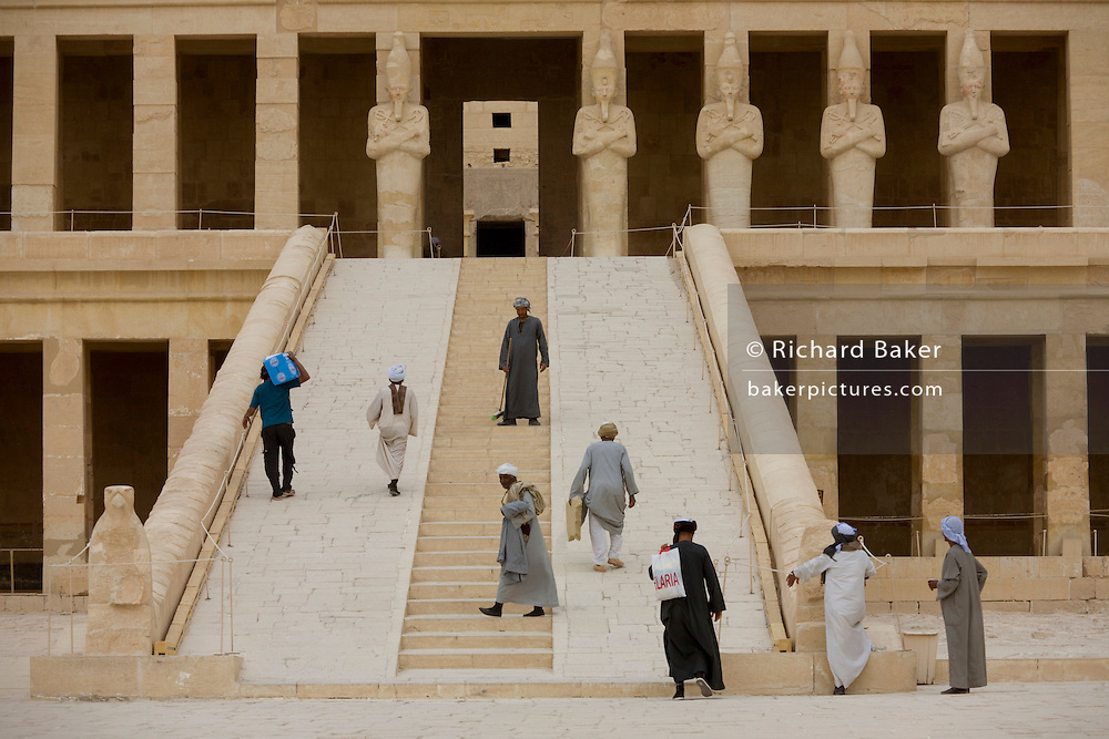 """Local guides and caretakers on the steps at the ancient Egyptian Temple of Hatshepsut near the Valley of the Kings, Luxor, Nile Valley, Egypt. The Mortuary Temple of Queen Hatshepsut, the Djeser-Djeseru, is located beneath cliffs at Deir el Bahari (""""the Northern Monastery""""). The mortuary temple is dedicated to the sun god Amon-Ra and is considered one of the """"incomparable monuments of ancient Egypt."""" The temple was the site of the massacre of 62 people, mostly tourists, by Islamists on 17 November 1997."""