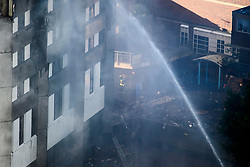 © Licensed to London News Pictures. 14/06/2017. London, UK. A Fireman watches over at the scene of a huge fire at Grenfell tower block in White City, London. The blaze engulfed the 27-storey building with 200 firefighters attending the scene. There were reports of people trapped in the building. Photo credit: Ben Cawthra/LNP