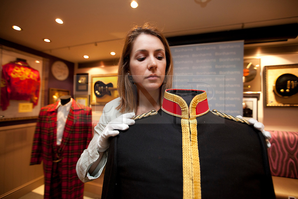 © Licensed to London News Pictures. 27/06/2012. LONDON, UK. A member of Bonhams staff tends to a jacket formerly owned by the late Michael Jackson at London's Hard Rock Cafe today (27/06/12). The jacket (est £8,000-12,000), worn by the singer when he met the King of Bahrain, and other pieces, were on display at London's Hard Rock Cafe ahead of an auction of entertainment memorabilia being held at Bonhams' Knightsbridge auction house on the 3rd of July. Photo credit: Matt Cetti-Roberts/LNP
