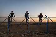 Facilities inside the camp are limited so children climb over the boundary fence in order to play football in an open space outside the confines of the camp.