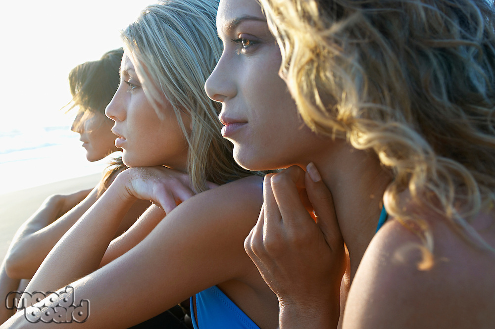 Three young women sitting side by side on beach looking at view close up