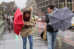 © Licensed to London News Pictures. 03/01/2016. London, UK. A woman struggles to control her umbrella during a gust of wind near Westminster in London.  London and the UK has experienced heavy rain and wind today. Photo credit : Vickie Flores/LNP