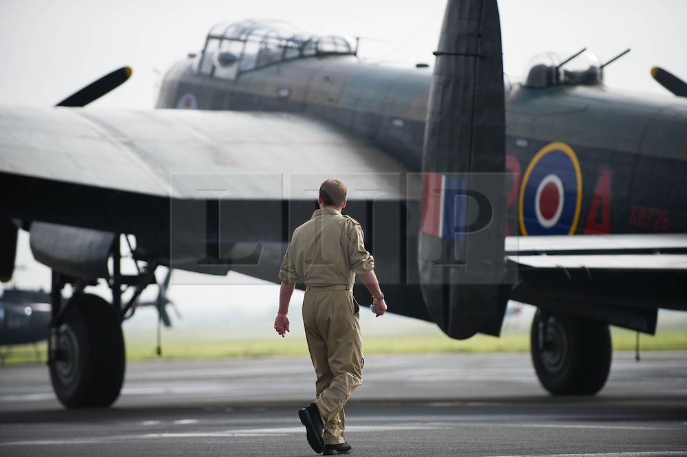 © Licensed to London News Pictures. <br /> 28/08/2014. <br /> <br /> Durham Tees Valley Airport, United Kingdom<br /> <br /> A member of the crew watches as one of only two remaining flying Avro Lancaster bombers is brought out of the hangar as it visits Durham Tees Valley airport today. <br /> <br /> The aircraft, 'Mynarski' is named after Pilot Officer Andrew Mynarski who flew with the Canadian Royal Air Force from the airport which was then called RAF Middleton St George.<br /> <br /> Pilot Officer Mynarski was posthumously awarded a VC after giving his life while trying to save a colleague when their Lancaster was shot down in June 1944.<br /> <br /> The famous World War Two aircraft is owned by the Canadian Warplane Heritage Museum and is beginning a 2-week tour of the UK.<br /> <br /> Photo credit : Ian Forsyth/LNP