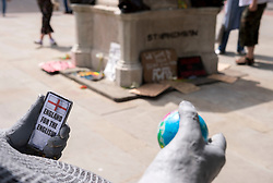 """© Licensed to London News Pictures; 15/06/2020; Bristol, UK. A new mystery statue of a caricature Englishman has been placed by the now empty Colston plinth seen in the background on the Monday morning after an """"All Lives Matter"""" protest at the weekend to """"defend the Cenotaph"""". The grey statue shows a bald man resting in a wheelie bin with the words """"Spoiler: St George was Turkish"""" on the front. He is holding a small globe in one hand and a mobile phone in the other hand with a screen showing the St George flag and words """"England for the English"""". The character wears a string vest over a beer belly and looks over to where Colston's statue was torn down from its plinth a week ago. The artist is not known but the statue looks similar to """"Ruth"""", a character who appeared on Victoria Street in April 2018. This comes just over a week after the statue of Edward Colston which has stood in Bristol city centre for over 100 years was pulled down by protestors and thrown in Bristol Docks during a Black Lives Matters rally and march through the city centre. The rally was held in memory of George Floyd, a black man who was killed on May 25, 2020 in Minneapolis in the US by a white police officer kneeling on his neck for nearly 9 minutes. The killing of George Floyd has seen widespread protests in the US, the UK and other countries against both modern day racism and historical legacies of slavery. Edward Colston (1636 – 1721) was a wealthy Bristol-born English merchant involved in the slave trade, a Member of Parliament and a philanthropist. He supported and endowed schools, almshouses, hospitals and churches in Bristol, London and elsewhere, and his name is commemorated in several Bristol landmarks, streets, three schools and the Colston bun. Photo credit: Simon Chapman/LNP."""