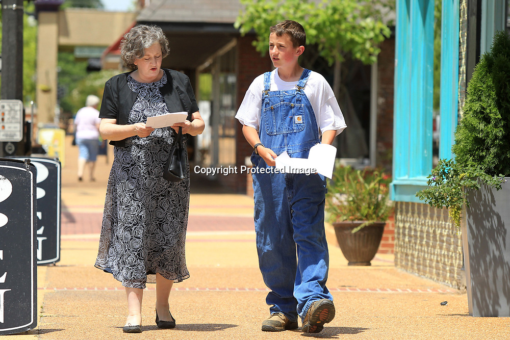 Jennifer Collins, as Elvis's mother Gladys, walks down main street with Tanner Palmer, as a young Elvis Presley, as they rehearse the reenactment of Elvis going to Tupelo Hardware and buying his first guitar from longtime Tupelo Hardware employee Forrest Bobo.