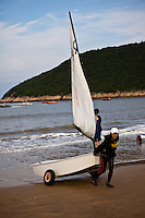 Young people sailing dinghys in the calm waters off songlanshan beach in Zhejiang province, China.