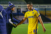 AFC Wimbledon midfielder Anthony Hartigan (8) shakes the hand of AFC Wimbledon Assistant Manager Nick Daws after the EFL Trophy match between Southend United and AFC Wimbledon at Roots Hall, Southend, England on 13 November 2019.