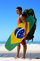 "Kite surfer with the brazilian flag painted on the board with ""praia e vento"" (beach and wind) instead of ""ordem e progresso""  in prainha beach near fortaleza"