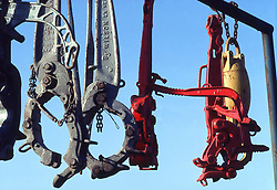 Stock photo of a large industrial tools hanging by chains from a bar