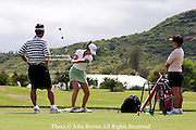Fifteen year old Michelle Wie is flanked by her mother Bo and father BJ as she uses a golf training aid on the practice range prior to the 2005 SBS LPGA Women's Open at Turtle Bay Resort in Kahuku, Hawaii.