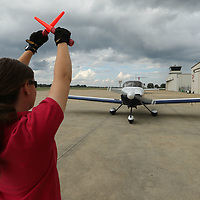 Cortney Norman directs a pilot where to park as he arrives at the Tupelo Airport for fuel and a hotel room.