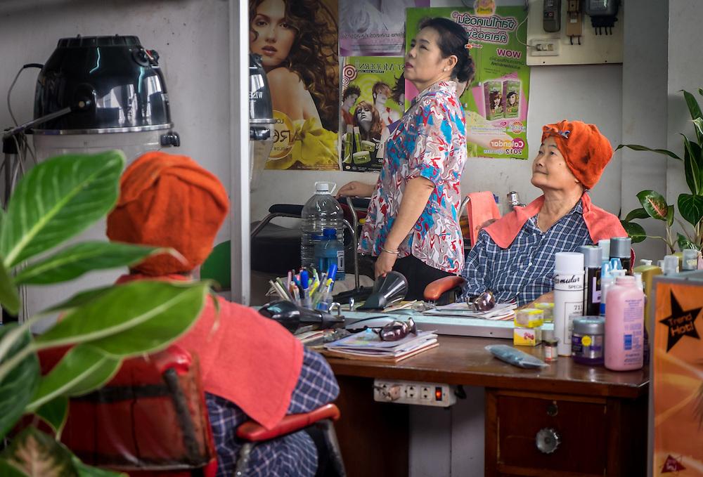 MAE KLONG - TAHILAND - CIRCA SEPTEMBER 2014: Thai women in a hair salon around the Maeklong Railway Market
