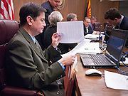 06 FEBRUARY 2012 - PHOENIX, AZ:   Arizona State Senator DAVID LUJAN (Democrat) reads paperwork before a Senate Judiciary Committee heading on loosening Arizona gun laws on Monday, Feb. 6. The Arizona State Senate's Judiciary Committee, chaired by Sen Ron Gould (Republican) debated several bills Monday that would loosen the state's gun laws, already among the loosest in the United States. One bill would allow anyone with a concealed carry permit to carry guns on the grounds of public universities. Universities could only ban guns if they provided secured gun lock boxes in each building. Universities, which are opposed to the legislation, say that the lock boxes would cost hundreds of thousands of dollars and that guns would make the campuses less safe. Most of the police departments in Arizona, as well as university student bodies, also oppose the legislation to allow guns on campus.    PHOTO BY JACK KURTZ