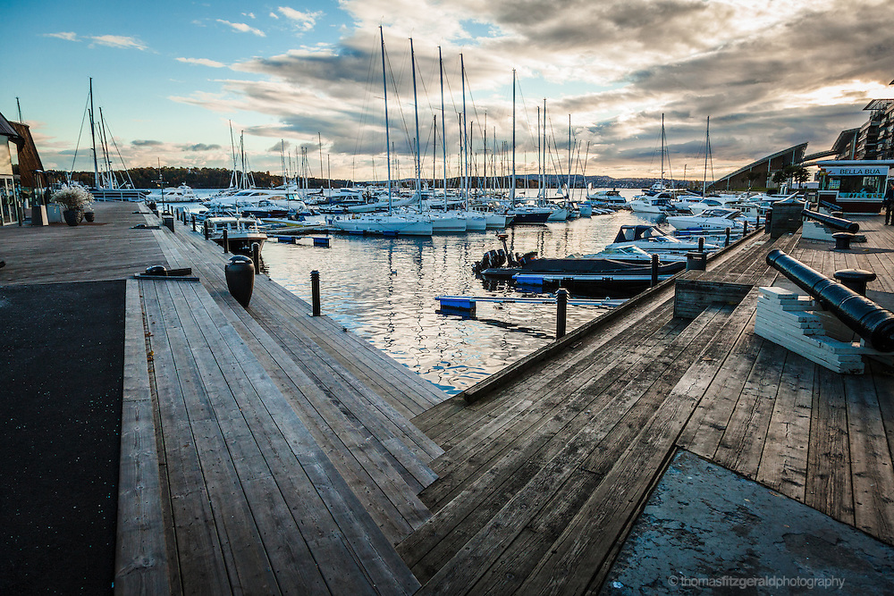 Oslo, Norway, October 2012: Boats moored in a marina in the oslo harbour as the setting sun casts a cool blue hue over the surroundings.EDITORIAL ONLY: This Image is only for Editorial Use