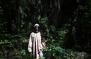 A village elder emerges from the forest near his community in the Casamance region of southern Senegal. The Jola (Diola) people are an ancient ethnic group that predominate in Casamance. Unlike most ethnic groups of West Africa, the Jola have no caste system. Their communities are based on extended clan settlements with a highly egalitarian organization and collective consciousness. Their culture is profoundly linked to nature and their environment. Most Jola communities sustain themselves through fishing, rice cultivation and palm oil and wine production. Casamance has a unique ecosystem of mangroves, forests and wetlands that has been significantly affected by climate change due to drought, the rise in sea levels and the salinization of waterways and soil, adversely affecting the way of life of its inhabitants. While communities are actively seeking partners and ways to improve their standard of living, they are determined to protect their sacred forests and natural environment. Diagho, Senegal. 10/11/2014.