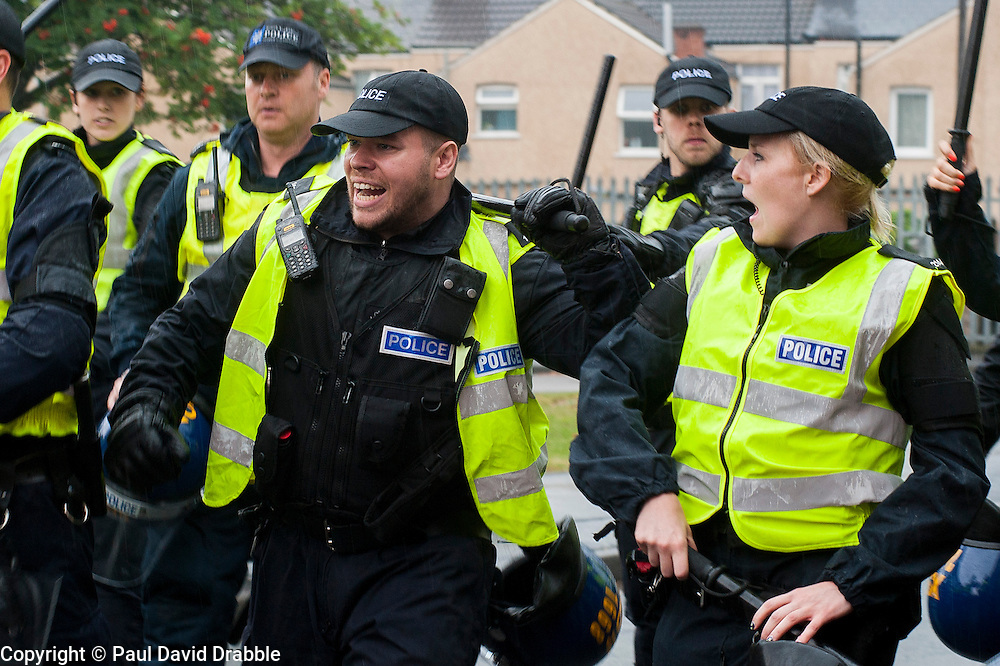 South Yorkshire PSU officers with battons drawn prepare to face UAF anti EDL protesters on a side street in Hexthorpe Doncaster South Yorkshire on Saturday Afternoon.<br /> The EDL and UAF are thought to have chosen Hexthorpe after recent media reports of tension between newly arrived Roma residents and the the local community<br /> 19 July 2014<br /> Image &copy; Paul David Drabble <br /> www.pauldaviddrabble.co.uk