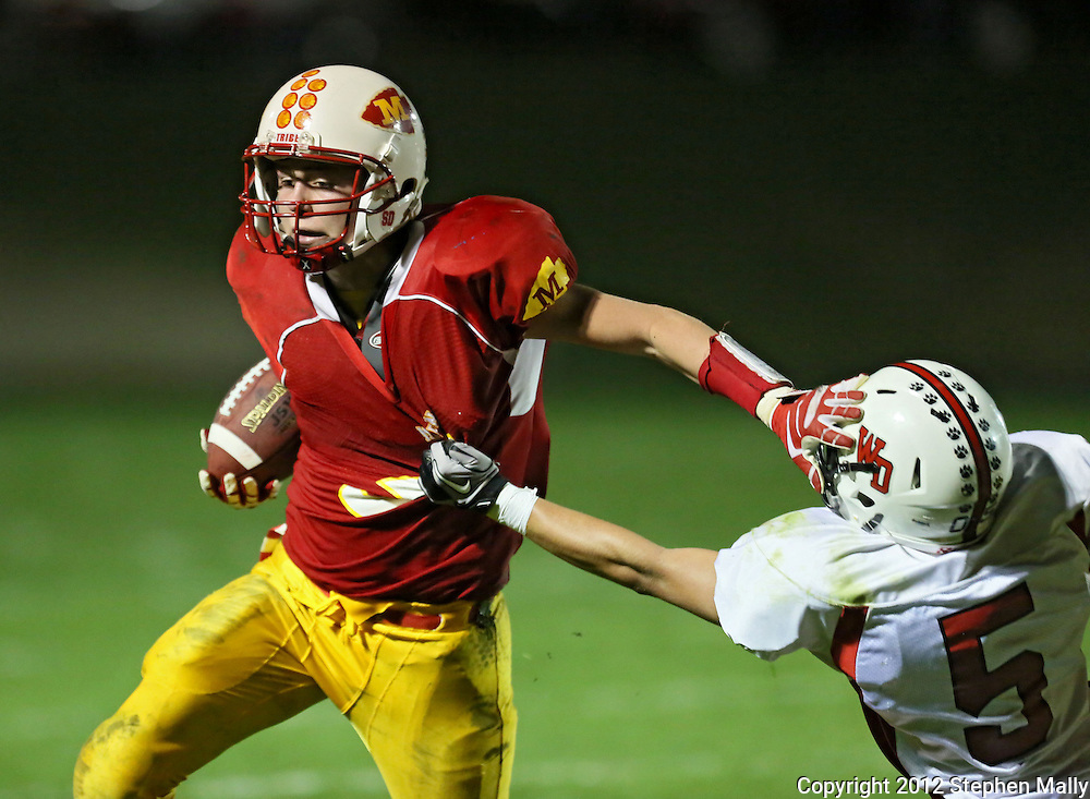 Marion's Tyler Gunderson (5) stiff arms Western Dubuque's Riley Pfieler (5) on a run during their first round playoff game at Thomas Park Field in Marion on Wednesday, October 24, 2012.
