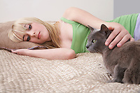 Teenage girl (16-17) lying on bed with cat