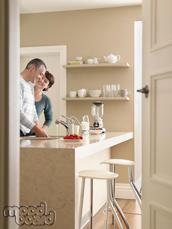 Smiling couple in kitchen seen through open door