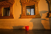 Shadow of a woman sweeping and bucket, sunrise light on orange wall, Swe Taw Pagoda, Mandalay