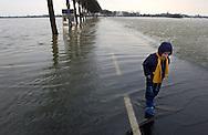 Nederland, Bergen (Limburg), 5 jan 2003.Hoog water in de Maas zorgt voor overlast door overstromingen. .Een jochie met laarzen aan loopt in het water dat het weggetje naar Bergen onbegaanbaar maakt. .Wateroverlast. .Foto (c) Michiel Wijnbergh/Hollandse Hoogte
