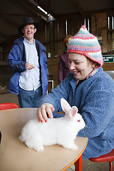 Woman with learning disability on trip to farm stroking a rabbit