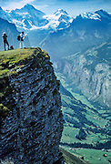 A hiker reads a map on  Männlichen mountain (7687 feet), below Mount Jungfrau (13,642 feet), above the Lauterbrunnen Valley (2612 feet), in Switzerland, Europe. Published in Wilderness Travel 1990, 1988 Catalog.