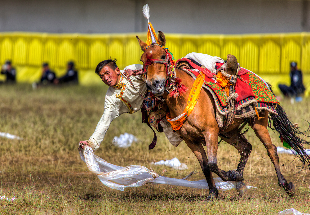 In Nagchu on an altitude about 4500m the Nomads get together for different games. One of these is a kind of Horse Race. They pick up from the ground white towels with money attached to it.