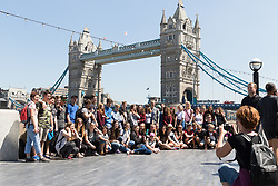 © Licensed to London News Pictures. 26/05/2017. LONDON, UK.  A large group of tourists take a photograph in front of Tower Bridge on the south bank during sunny weather at lunchtime. The capital has experienced another day of hot and sunny weather. Photo credit: Vickie Flores/LNP