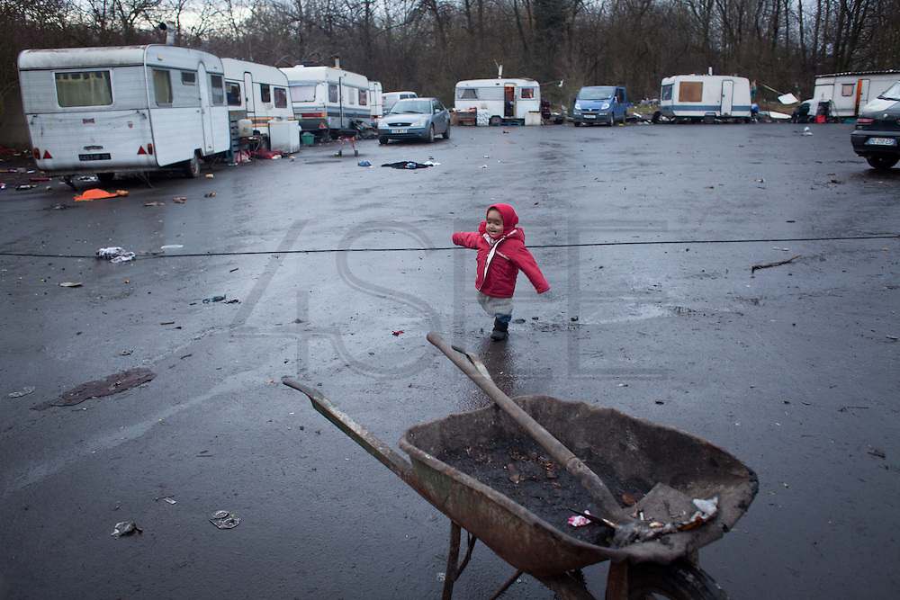 A little girl is playing in a gypsy settlement on the outskirts on Lille. // France is the land of destination of many Roma people in their diaspora across Europe, who live camped in many settlements at the outskirts of cities. In 2013, the French Government has expelled thousands of Gypsies from the East as in 2010, 2011 and 2012, this time without any financial aids. Many Roma live afraid to be expelled but they remain in the French country with the hope of receiving some kind of aid. Outskirts of Lille, France. December 2013.
