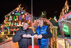 © Licensed to London News Pictures. 01/12/2019. Bristol, UK. PAUL BRAILSFORD and LEE BRAILSFORD press the plunger to switch on the Christmas lights on the Brailsford family home in Trevisa Grove. It started in 1994 when brothers Paul and Lee Brailsford were teenagers and has now become a festive highlight in the name of raising money for one of Bristol's most loved charities, Wallace & Gromit's Grand Appeal which supports sick children and their families at Bristol Children's Hospital. The Brailsford's lights are recognised as one of the largest private Christmas lights displays in the UK, the family has so far raised £68,000 from generous public donations for the Bristol Children's Hospital charity. The spectacle of over 50,000 Christmas lights takes six weeks to build and boasts 15 Santas, 10 reindeer, 10 snowmen, 50 rope-light shapes, trains, elves and a life-size nativity powered by 100,000 LED lights. The house will light up every night until Thursday 2 January 2020 from 5pm to 10pm. Wallace & Gromit's Grand Appeal is the dedicated Bristol Children's Hospital charity. It runs a multi-million-pound portfolio of investment in partnership with the children's hospital and its Neonatal Intensive Care Unit at St Michael's Hospital, Bristol. Photo credit: Simon Chapman/LNP.