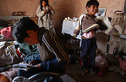 Potosi, Bolivia.<br /> The Benabides family home. When their father, a miner,  died 5 years ago of silicosis, five children live with their mother in this one room, two bed house. They sleep three to a bed. Beimar, 8, looks over his homework.
